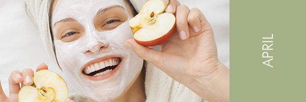 junge Frau mit Gesichtsmaske und Äpfeln in den Händen