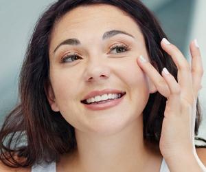 junge Frau trägt Augencreme auf