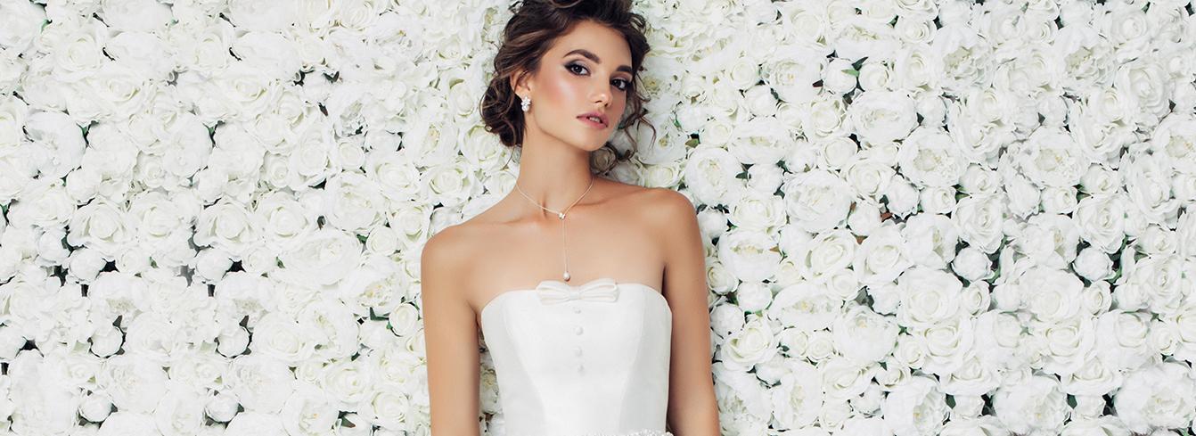 junge Braut vor weißen Rosen