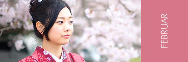 junge asiatin im Kimono vor Kirschblüten